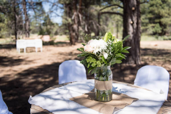 Simple dinging atmosphere for an outdoor woodland wedding. Old wire spools as tables, white chair covers and babies breath. You just can't go wrong.