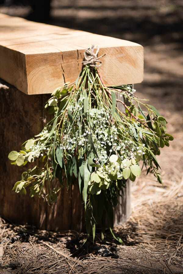 I love themed weddings. This outdoor woodland themed wedding is amazing. You must see all the sweet details! These simple swags hung on rustic benches is just one amazing detail.