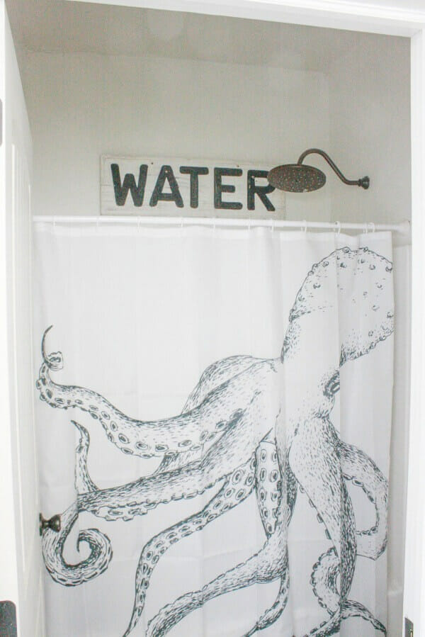 This reclaimed water sign is the perfect addition to this budget friendly bathroom makeover! | Twelveonmain.com