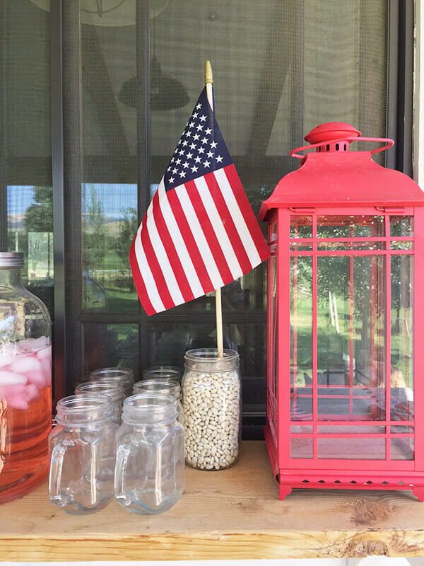 Farmhouse style patriotic outdoor tablescape for the 4th of July. Striped fabric, seagrass placemats, and red, white and blue, all on a chippy farmhouse table.