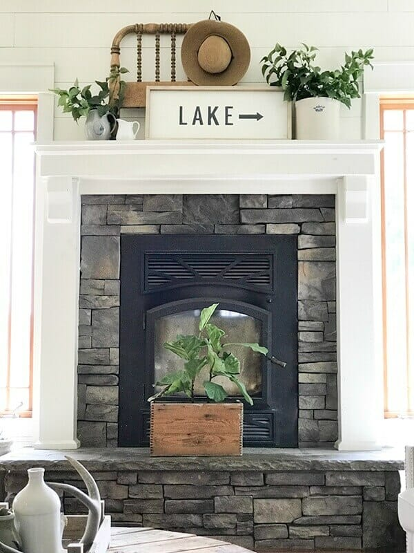 Farmhouse living room summer decor complete with large farmhouse signs, pottery, rustic wood, and fresh lilac cuttings. A touch of navy blue accents finishes off the space.