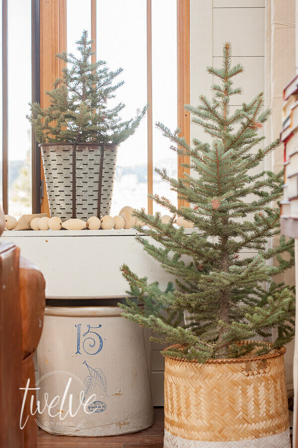 Mini Christmas trees and vintage crocks are the perfect farmhouse Christmas living room decor.