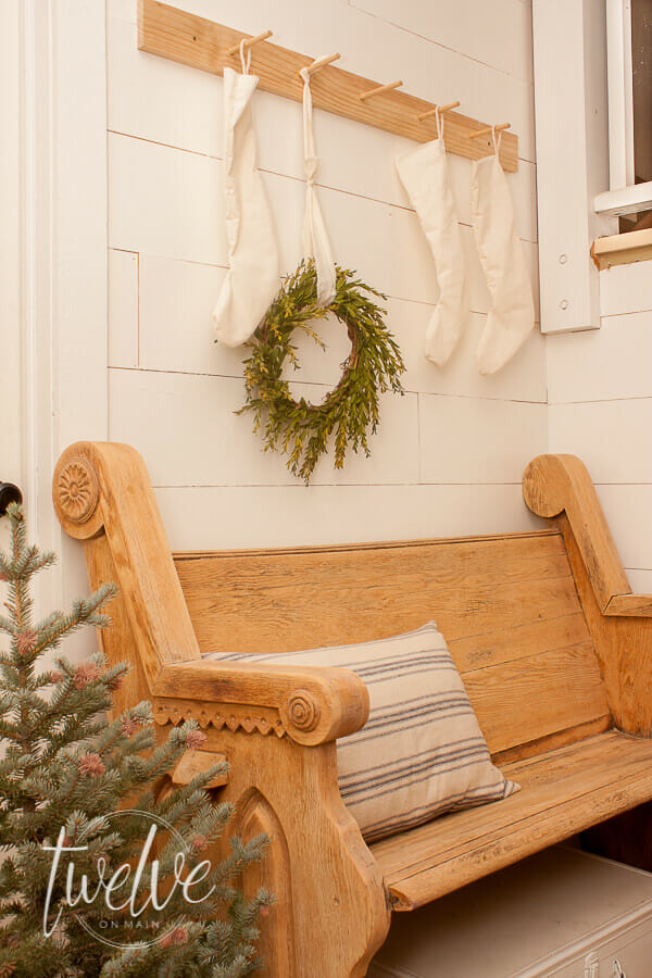 Create beautiful farmhouse Christmas entry decor with a vintage church pew, simple white Christmas stockings, a boxwood wreath, grainsack pillows, and a fresh blue spruce Christmas tree.