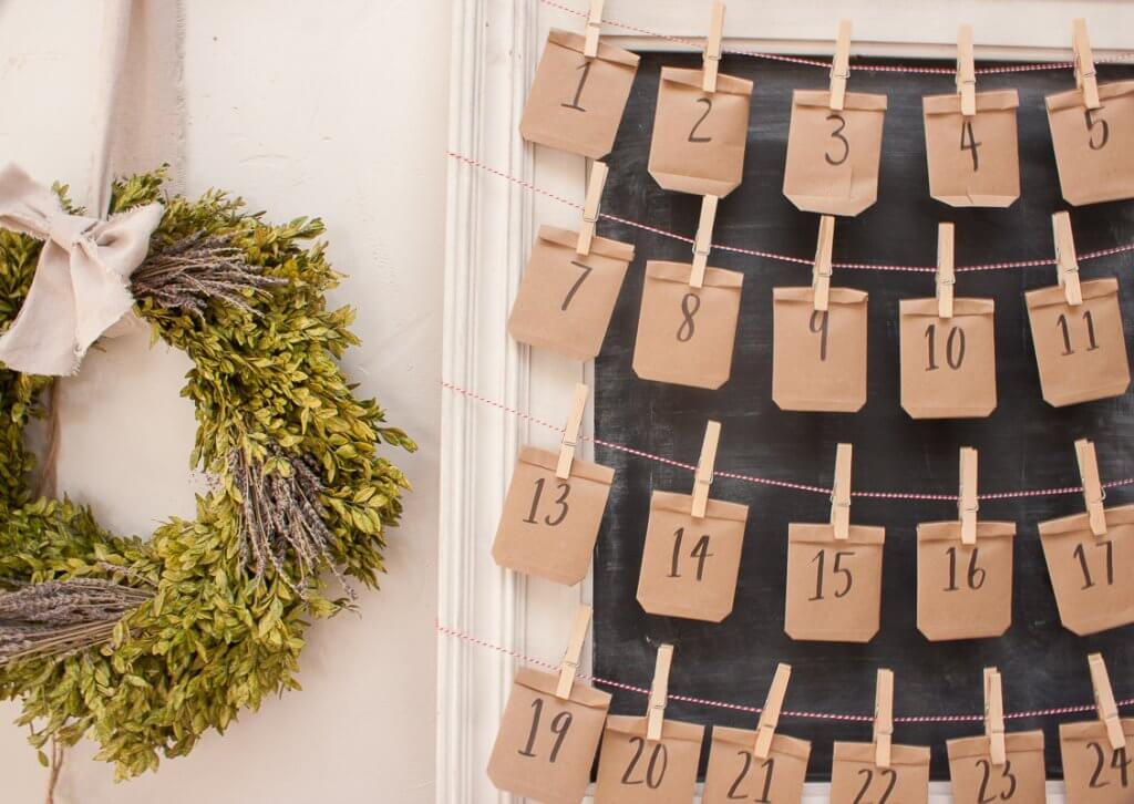 Simple framed chalkboard advent calendar made with simple paper envelopes and clothespins to hang them.