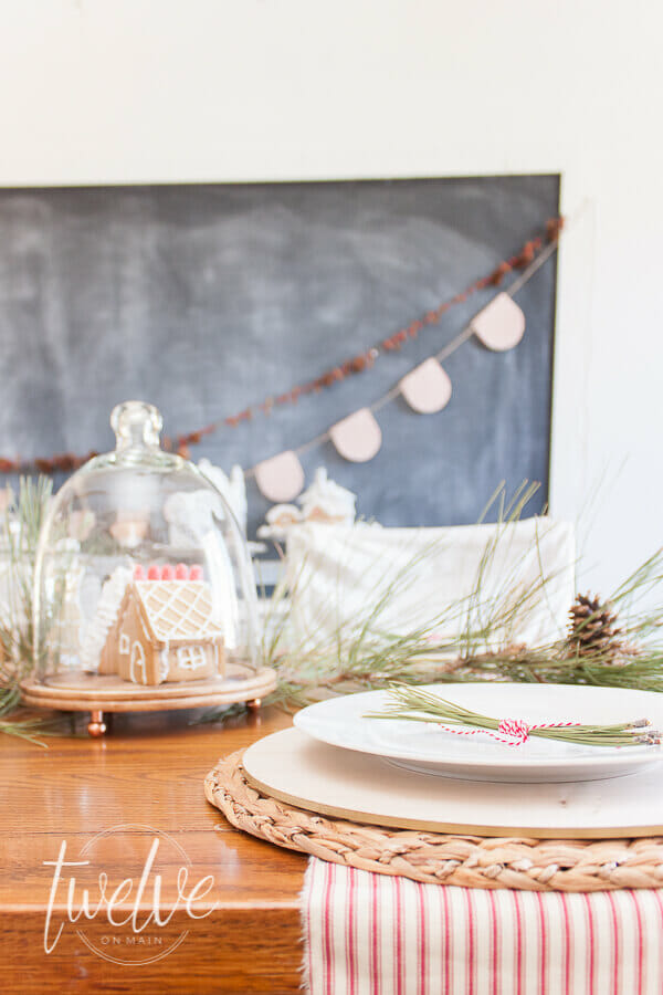 Mini gingerbread houses in glass cloches on the table, red and white Christmas garland along the chalkboard, vintage pottery, Rae Dunn Clay pottery, and pine boughs.