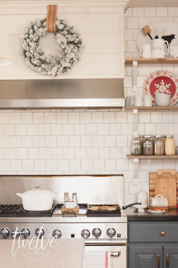 Red and white farmhouse Christmas kitchen decor complete with aRae Dunn Clay pottery, a vintage turkish rug, decorated open shelves, flocked Christmas wreath, and other simple farmhouse Christmas decor pieces.