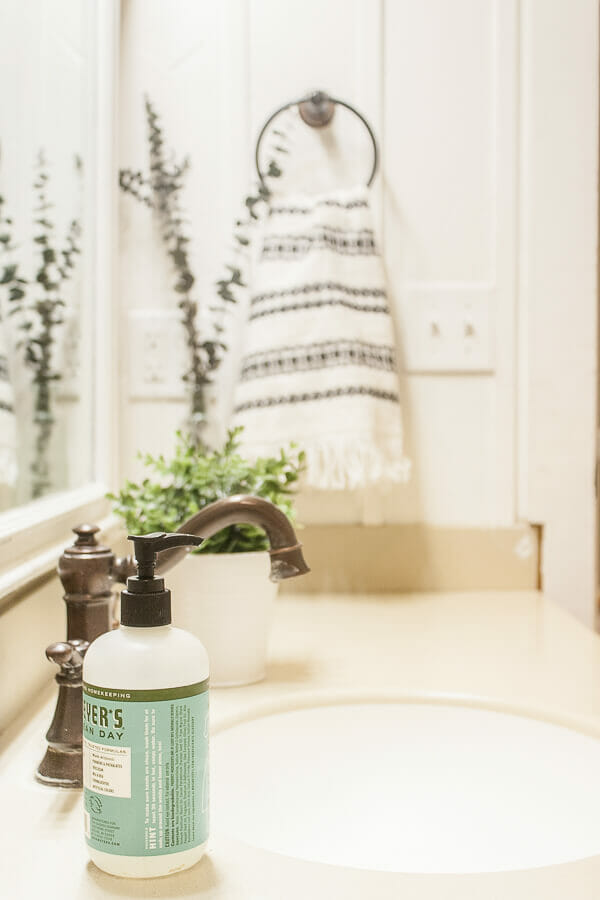 Mrs Meyer hand soap and a tribal inspired hand towel added so much to the bathroom decor in this simple kids bathroom. A little greenery never hurt either!