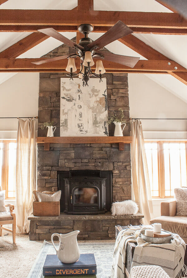 Farmhouse art ona stacked stone fireplace, exposed beams, dropcloth curtains, and cozy ticking stripe throw pillows and blankets create the perfect mood for anyone looking to just relax for a bit.