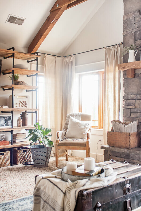 I love the combination of industrial style shelves along with farmhouse accents in this farmhouse living room.
