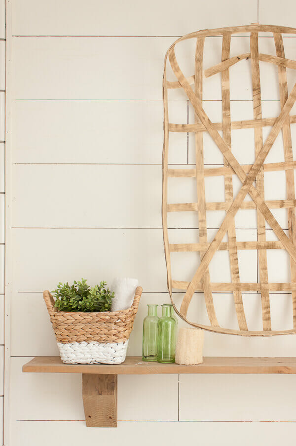 Rustic wood shelves, tobacco basket, shiplap and subway tile in the master bathroom. So very farmhouse style!