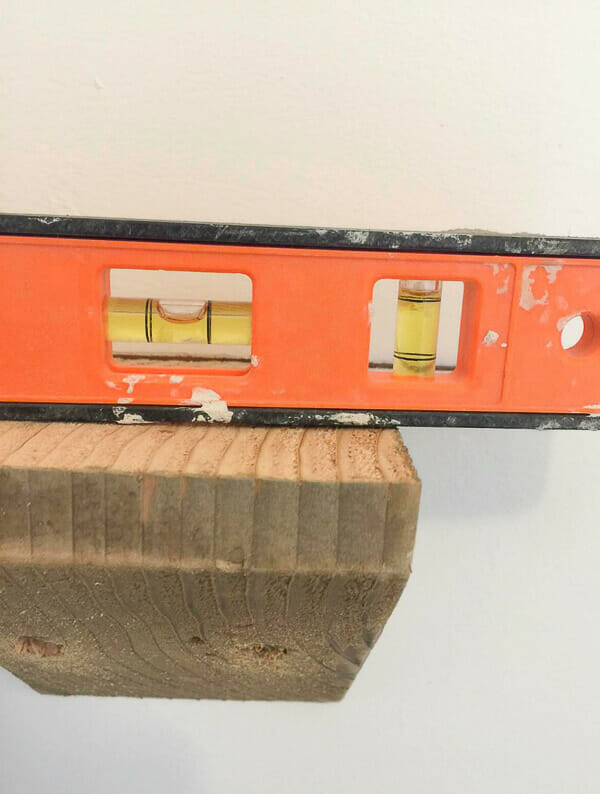 Tips on installing reclaimed rustic wood shelves with handmade corbels.