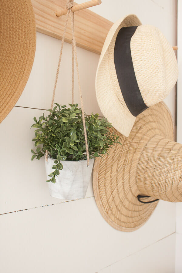 Shiplap, a vintage church pew, straw hats, an adorable dog pillow and a custom piece of artwork makes this spring entryway decor stand out!