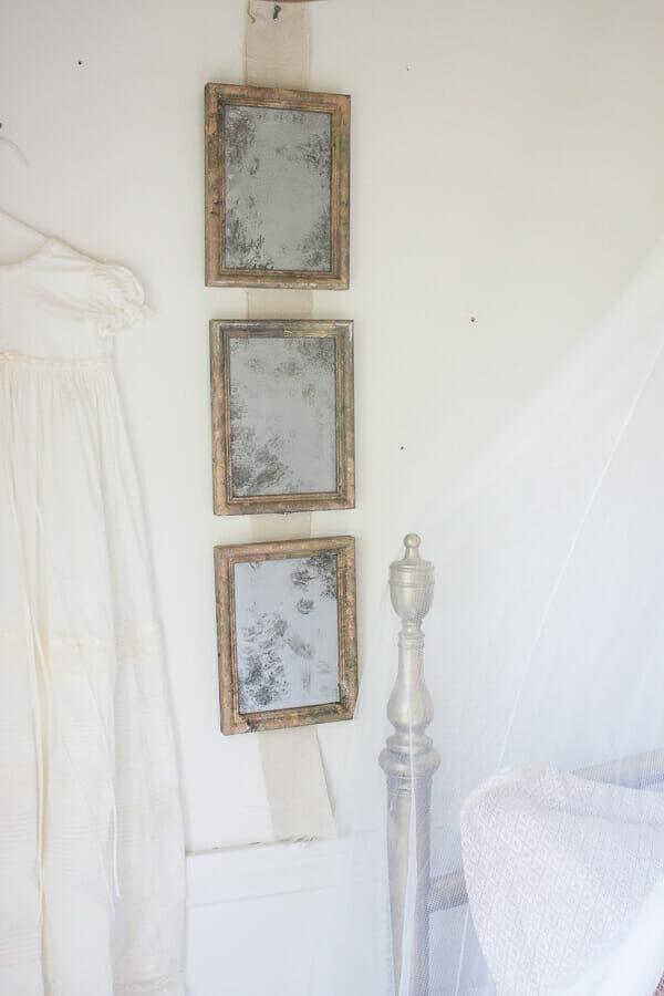 Little girls vintage french bedroom with vintage glass light and aged vintage mirrors made from old thrift store picture frames.