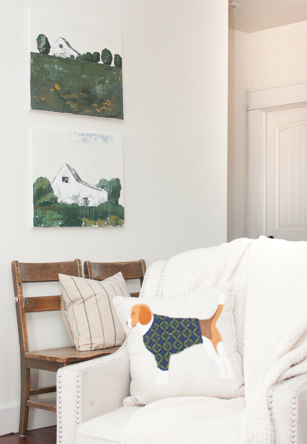 Farmhouse artwork in the living room. Vibrant green landscape with white farmhouse.