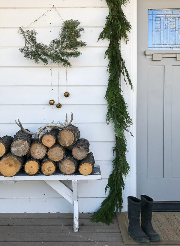 Scandinavian Christmas porch decor including fresh garland, handmade nordic wall hanging, and simple elements that keep Christmas calm this year