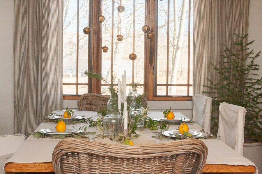 Scandinavian style Christmas table with natural elements, whites, fresh pines, and bells hanging from the chandelier