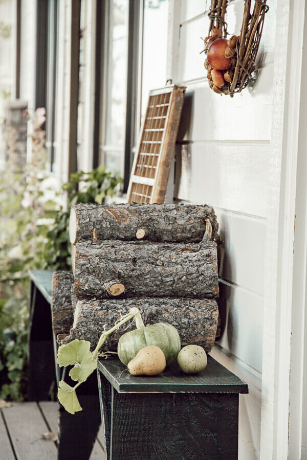 Simple porch decor for fall. Stacks of firewood, handmade wreaths, and a simple pumpkin or two. Neutral fall decor on the porch.
