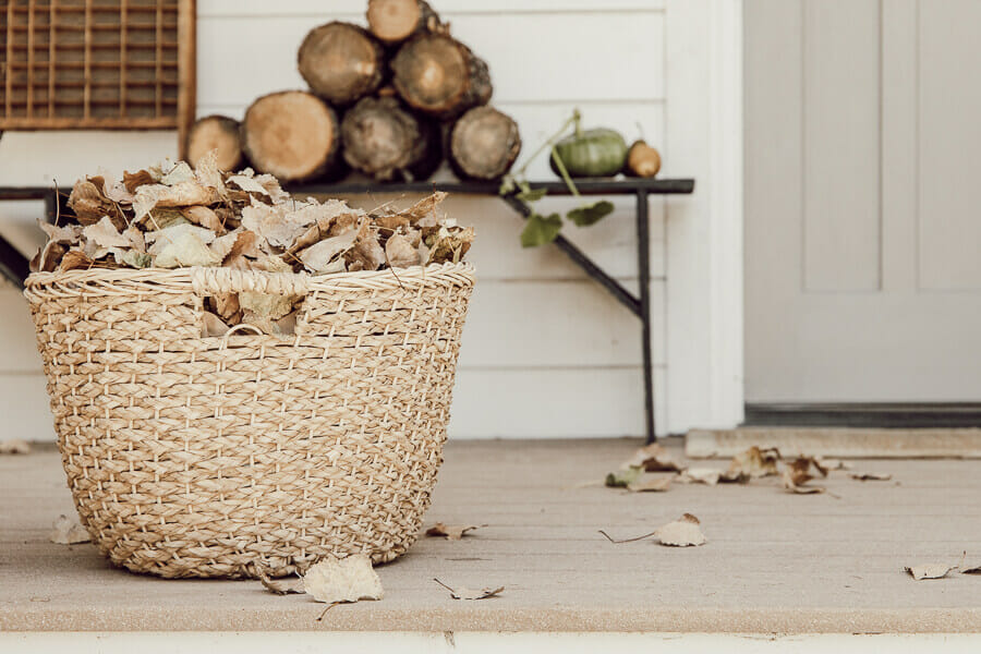 Welcome to my home for fall. My porch is decked out with simple fall items. A black primitive bench, handmade apple and walnut fall wreaths, stacks of firewood, and baskets of leaves. A lone pumpkin rounds out the decor.