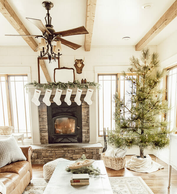 Christmas living room decor including a stacked stone fireplace, antique wood mirrors, deer antlers, a Ponderosa pine tree all decorated for Christmas