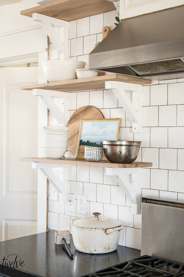 Printable art in the kitchen, on open shelving, styled with butcher blocks cutting boards, copper bowls, and brick style subway tile backsplash