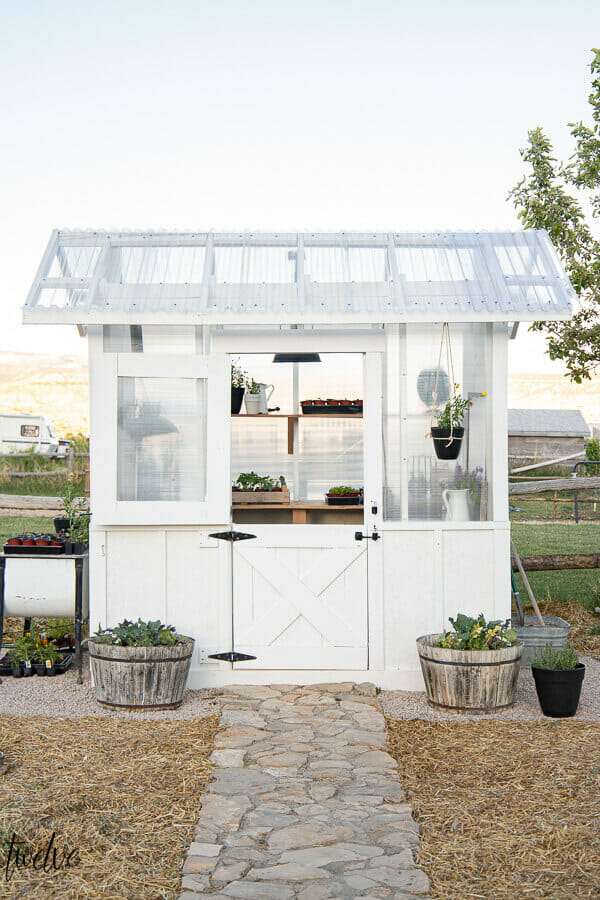 Amazing white DIY greenhouse design complete with a dutch door for ventilation, gorgeous lighting, wood shelves, and so much more. Can you believe this is also super affordable? Check it out!