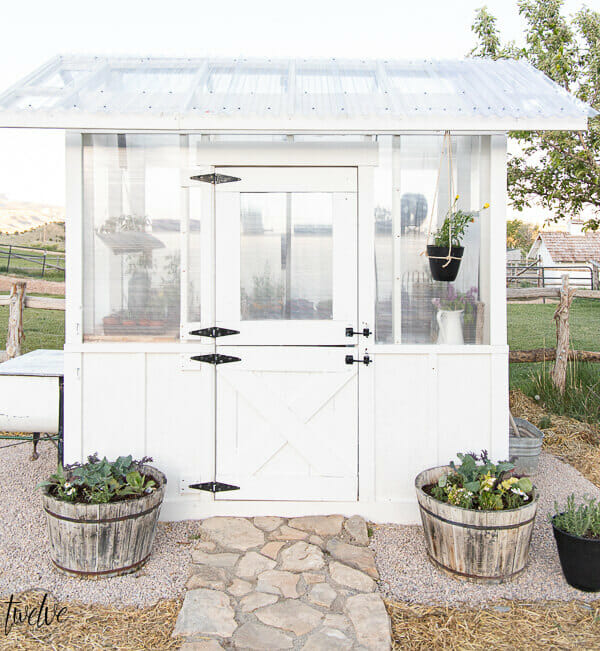 Our DIY greenhouse reveal! Check out all the amazing details of this simple, but gorgeous greenhouse design. A dutch door, board and batten, a gorgeous black light fixture and so much more!