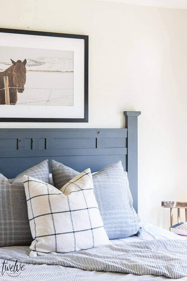 Teenage boys bedroom complete with simple white walls, ticking strip bedding, grey plaid pillows and some horse photography to round it out.