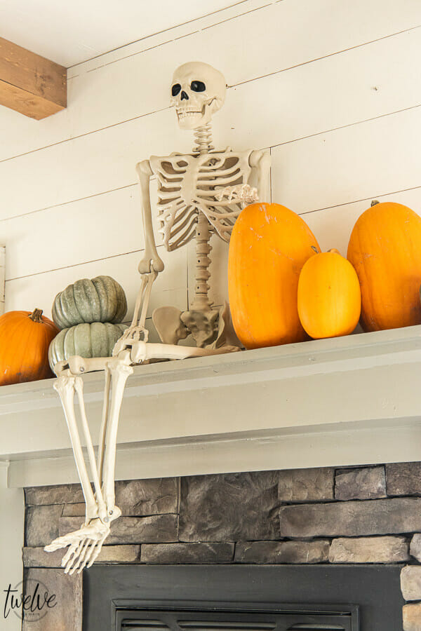 What a fun way to decorate for Halloween! Check out this amazingly simple and conversation starter Halloween mantel!  This is so fun!  A full sized posable skeleton along with some real pumpkins are the perfect Halloween mantel accessories!